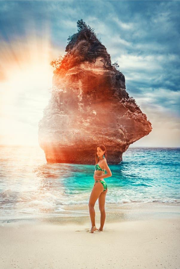 摆在在岩石和日落背景的海滩的绿松石比基尼泳装的美丽的年轻女人  图库摄影