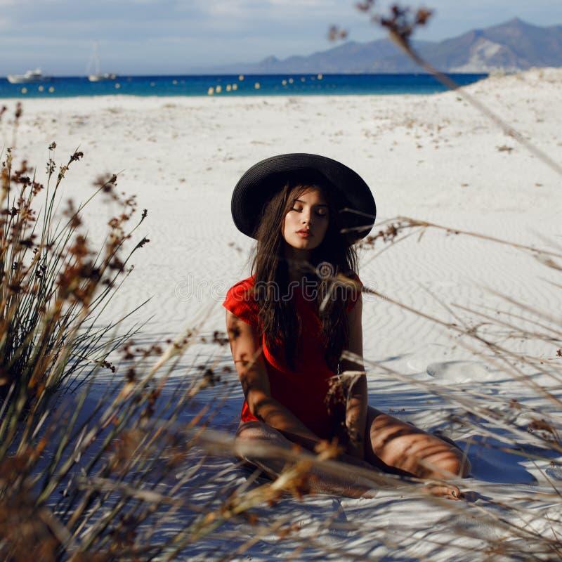 摆在在沙子的海滩的性感的女性模型在有黑帽会议的红色泳装,有闭合的眼睛的,在海景 库存图片