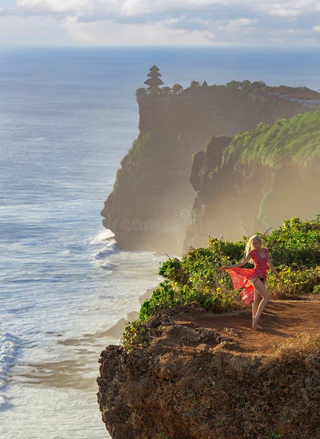 摆在在海洋上的峭壁的红色礼服的妇女 图库摄影