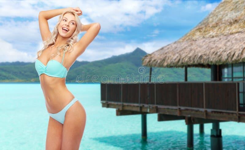 摆在在海滩的比基尼泳装的年轻女人 免版税库存图片
