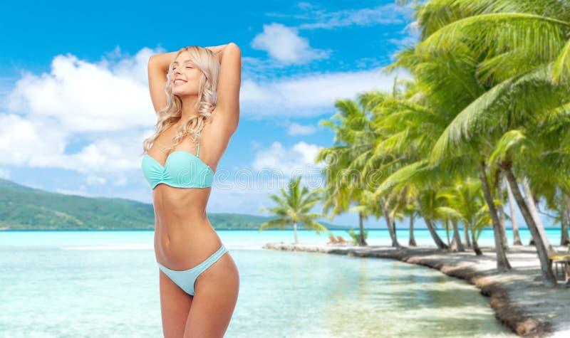 摆在在海滩的比基尼泳装的年轻女人 库存照片