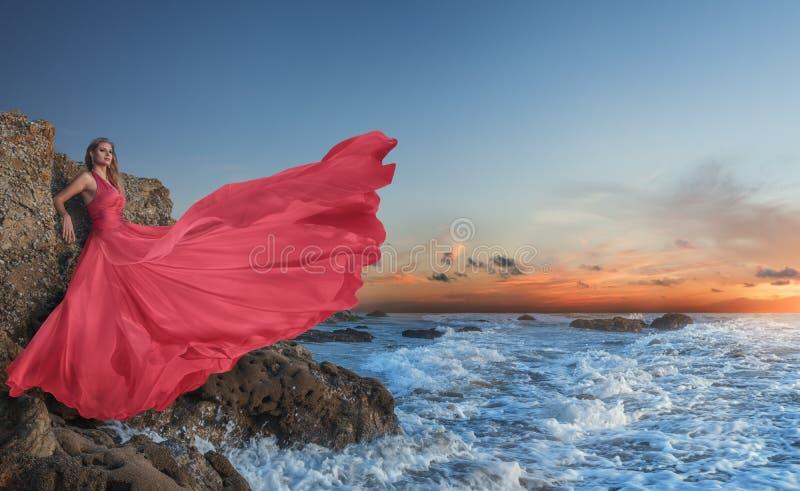 摆在在海滩的豪华长的礼服的美丽的年轻女人 库存照片