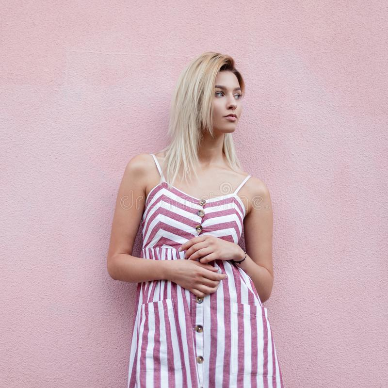 摆在在街道上的桃红色葡萄酒墙壁附近的时髦桃红色镶边礼服的时兴的俏丽的年轻女人金发碧眼的女人在城市 库存图片