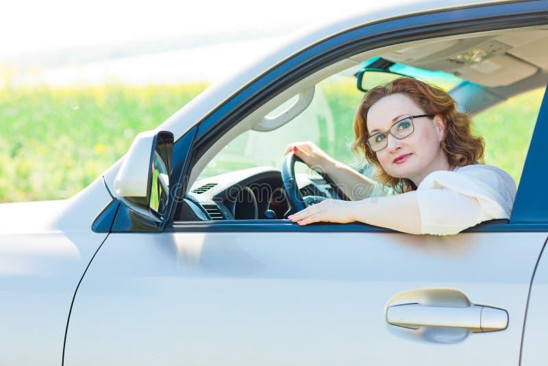 摆在在驾驶席的汽车的可爱的妇女 库存照片