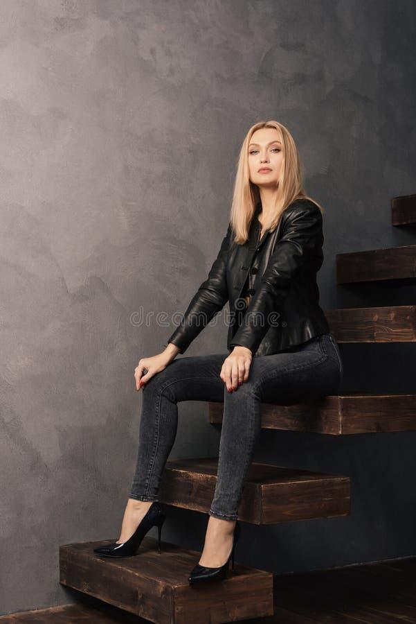 摆在坐一架木悬臂式梯子的黑皮夹克和牛仔裤的美丽的妇女 免版税图库摄影