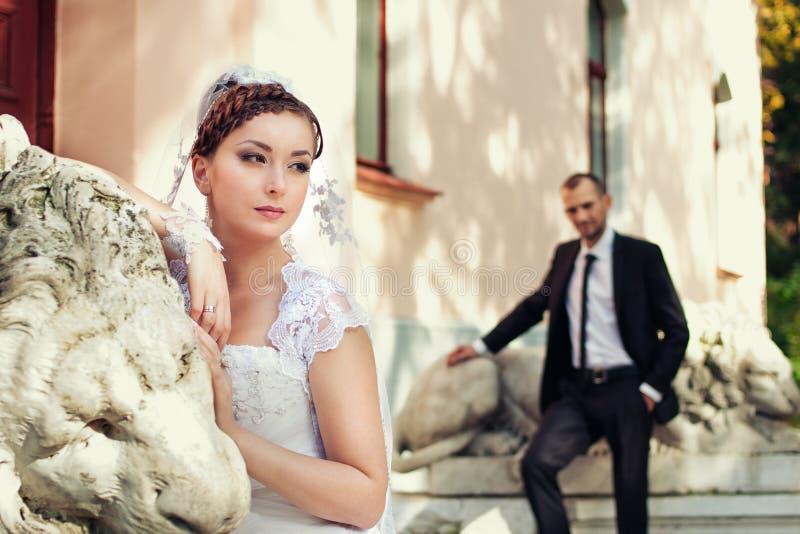 摆在城堡附近的新娘和新郎 免版税库存图片