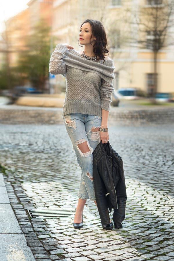 摆在城市的外套的画象相当肉欲的妇女 免版税库存图片