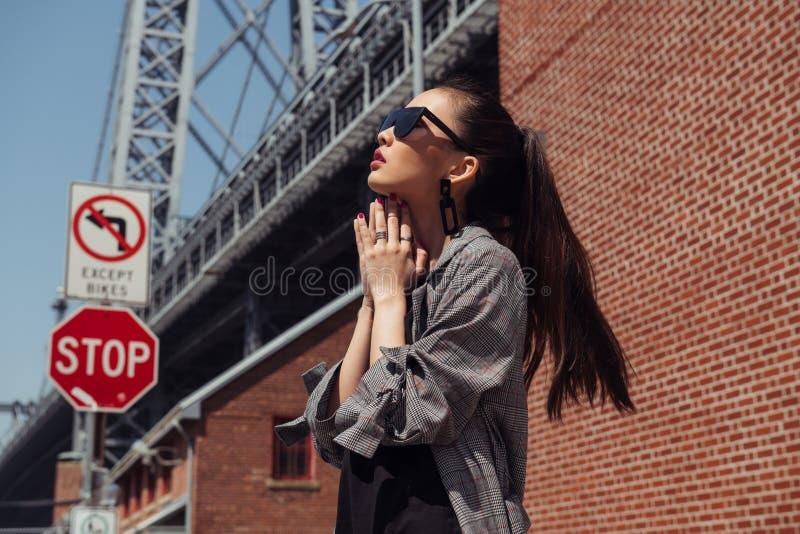 摆在城市街道上的美丽的亚裔时装模特儿女孩戴时髦的牛仔布衣裳和太阳镜 免版税库存照片