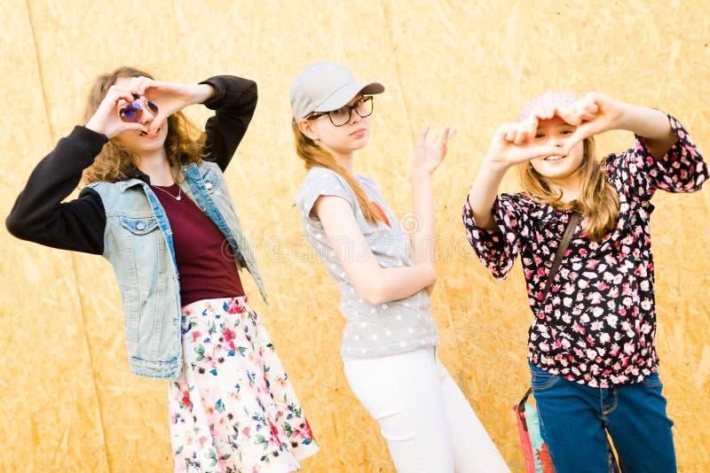 摆在城市街道-心形上的三少女-乐趣 免版税库存照片
