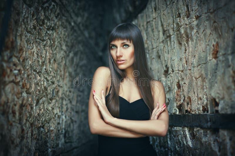 摆在墙壁之间的俏丽的少女室外生活方式画象,佩带在都市背景的时尚样式 被定调子的创造性 库存照片