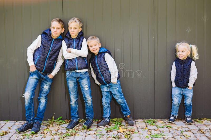 摆在墙壁成长背景的三个兄弟和姐妹的滑稽的白种人大家庭身分在充分的成长的 相等地 免版税图库摄影