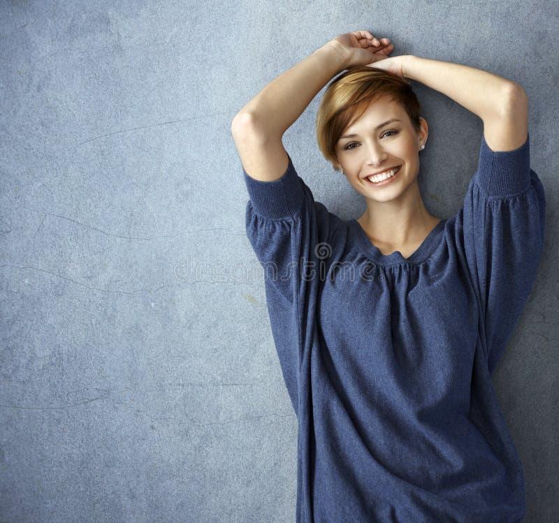 摆在墙壁的蓝色牛仔裤的愉快的少妇 库存图片