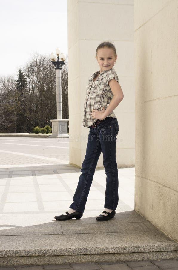 摆在墙壁附近的小女孩 免版税库存照片