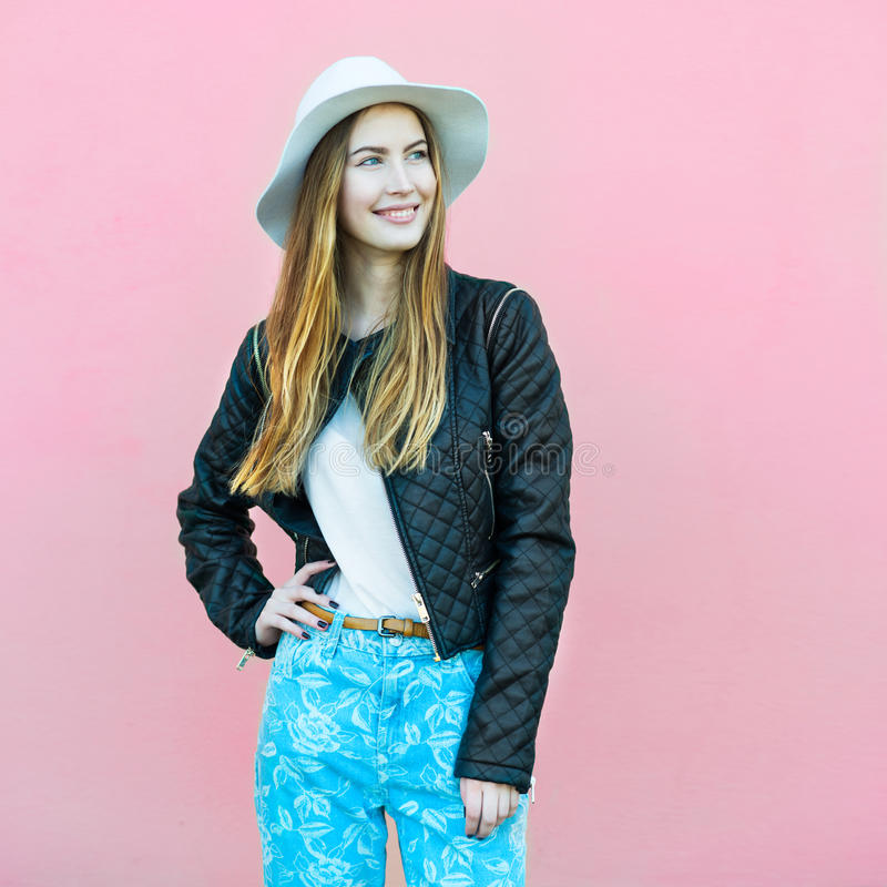 摆在墙壁附近的年轻愉快的时尚博客作者女孩穿偶然街道样式服装 库存图片