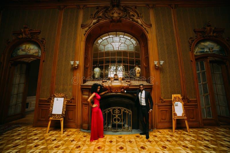 摆在壁炉的美好的非洲夫妇 豪华剧院内部 库存图片