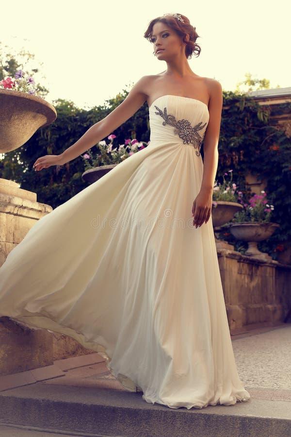 摆在夏天公园的典雅的婚礼礼服的美丽的新娘 免版税库存图片
