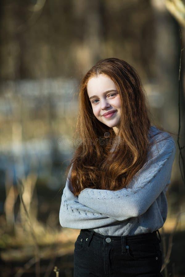 摆在夏天公园的逗人喜爱的愉快的十几岁的女孩 库存照片