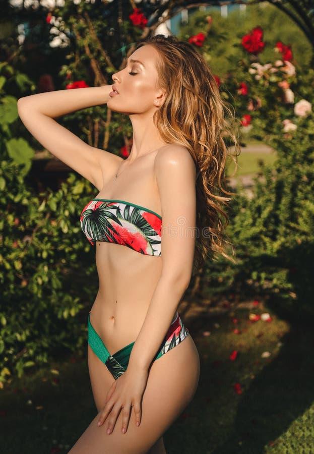 摆在夏天开花的典雅的游泳衣的美丽的女孩 库存照片
