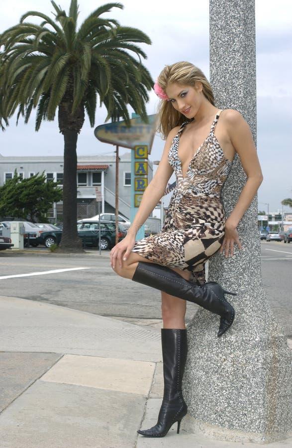 摆在外面在街道上的美丽的白肤金发的女孩 库存照片