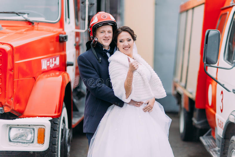 摆在大红火卡车附近的愉快的婚礼夫妇 消防员的盔甲的新郎 免版税库存图片