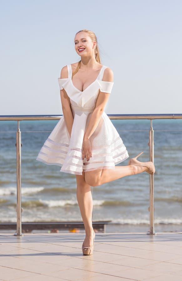 摆在大阳台的一个美妙的夫人 明亮的天空背景的一位微笑的女性 一件短的白色礼服的一个时髦的女孩 免版税库存图片