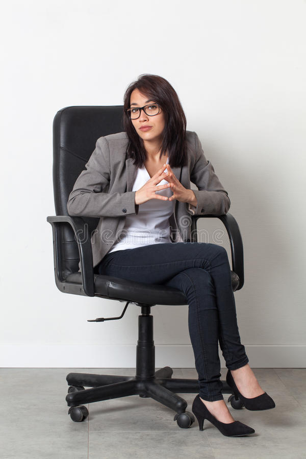 摆在她起始的工作的办公室椅子的耐心女实业家 免版税库存照片