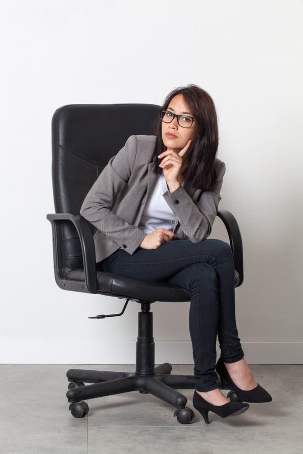 摆在她起始的工作的办公室椅子的年轻女实业家 库存图片
