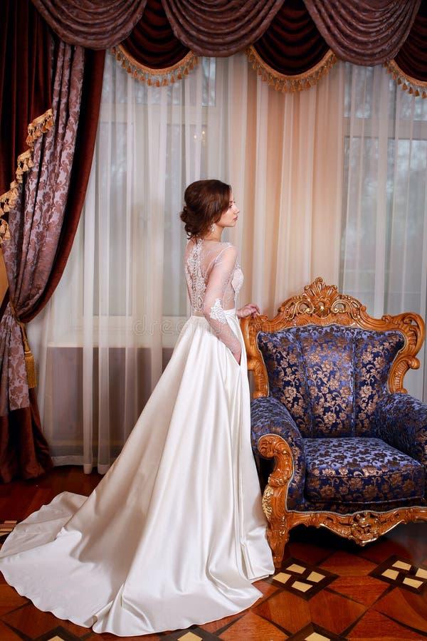 摆在婚礼礼服的美丽的少妇 免版税库存照片