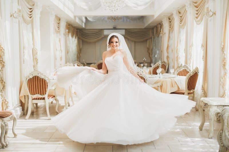 摆在婚礼礼服的美丽的新娘在时尚旅馆里 免版税库存图片