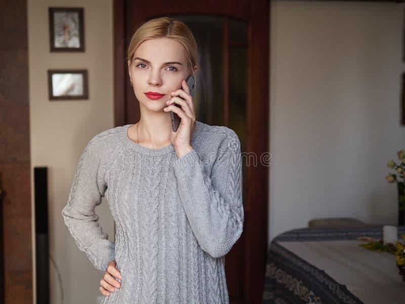 摆在家庭办公室室的年轻严肃的可爱的白肤金发的企业夫人举行手机回答的电话 免版税图库摄影