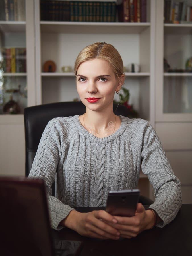 摆在家庭办公室室的年轻严肃的可爱的白肤金发的女商人坐在有拿着手机的笔记本的书桌 免版税库存照片