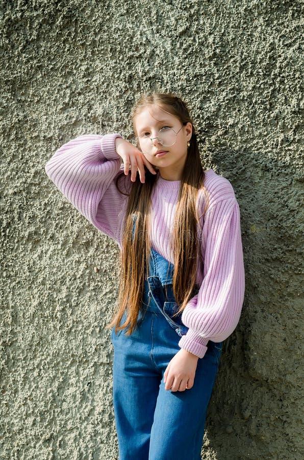 摆在对灰色街道墙壁的青少年女孩 免版税库存图片