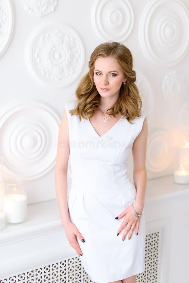 摆在对白色墙壁的一件白色礼服的美丽的年轻女人 一个好女孩的照片一件白色礼服的在市场对面 免版税库存照片