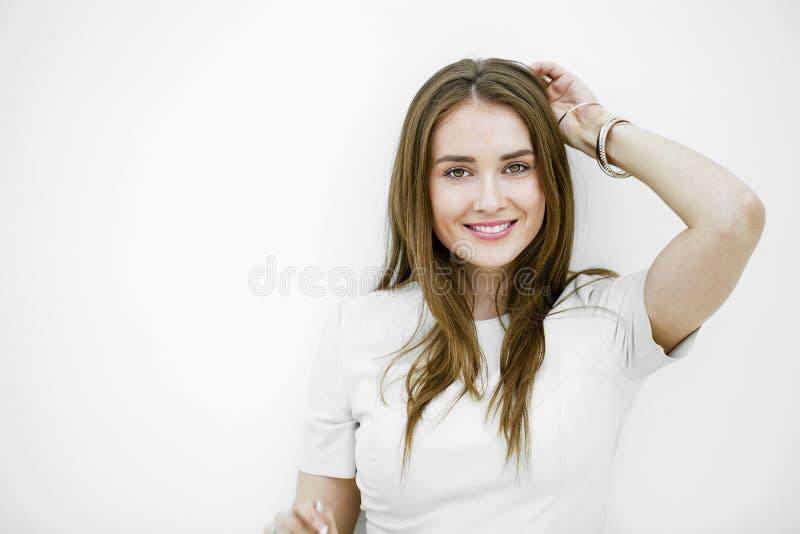 摆在对白色墙壁的美丽的年轻愉快的妇女 免版税库存图片