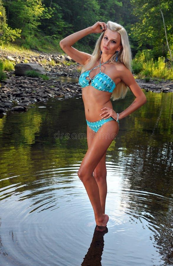 摆在山河的蓝色比基尼泳装的妇女 免版税图库摄影