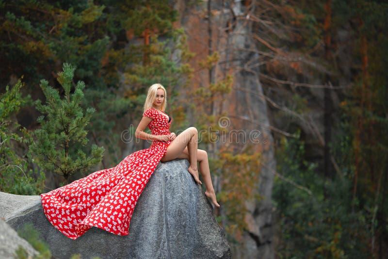 摆在山的红色礼服的美丽的妇女 免版税库存图片