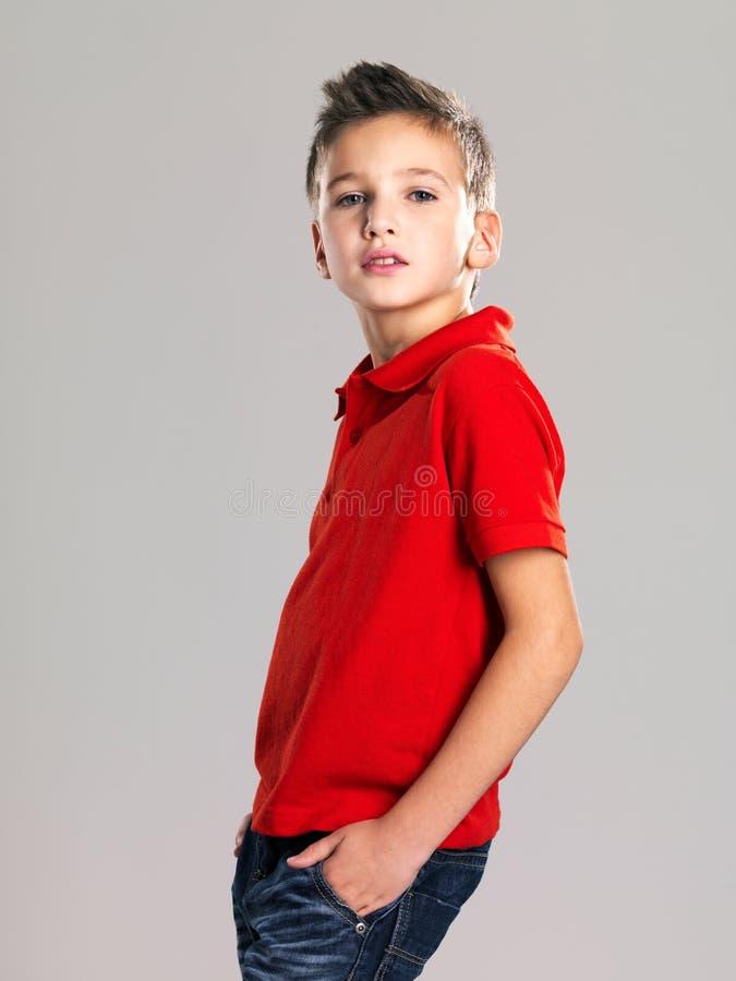 摆在工作室的俏丽的男孩作为时装模特儿。 免版税库存照片