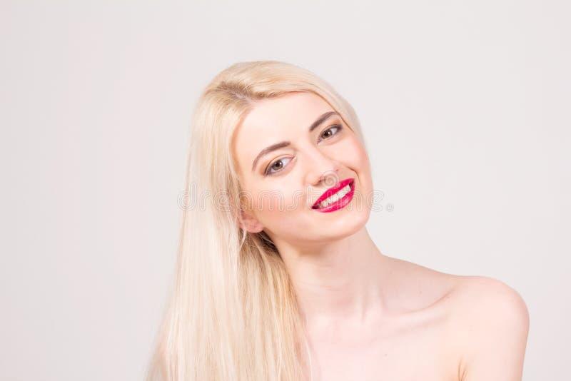 摆在工作室的时装模特儿 有长期平直的金发、白色牙、红色嘴唇和构成的微笑的美丽的妇女 图库摄影