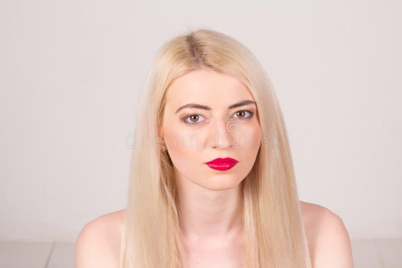 摆在工作室的时装模特儿 有长期平直的金发、红色嘴唇和构成的美丽的妇女 免版税库存图片