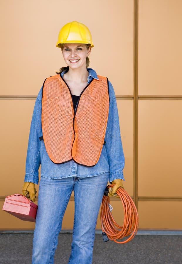 摆在工作者的建筑女性安全帽 免版税库存照片