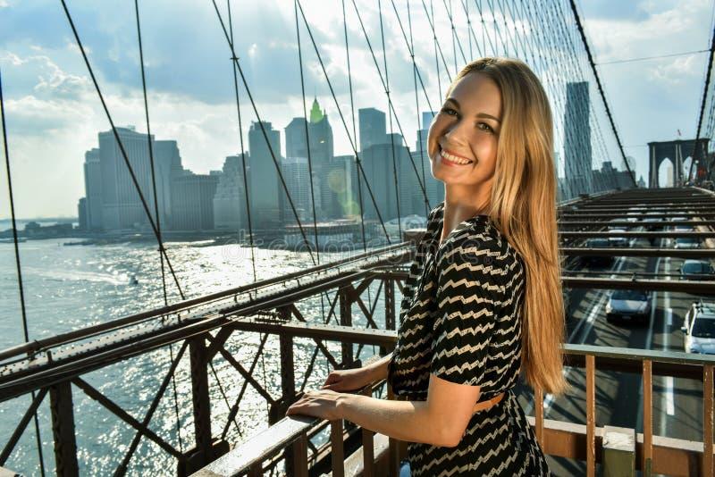 摆在布鲁克林大桥的美丽的微笑的少妇室外时尚画象  库存照片
