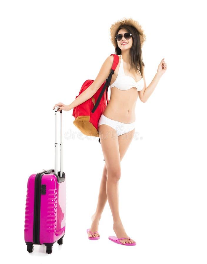 摆在带着旅行手提箱的比基尼泳装的妇女 库存图片