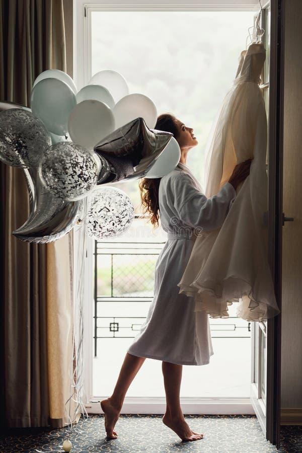 摆在帷幕下的白色礼服的美丽的性感的新娘 免版税库存图片