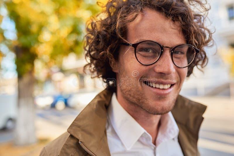 摆在年轻愉快的商人特写镜头水平的画象戴眼镜的微笑和户外 秋天街道的男生 库存照片