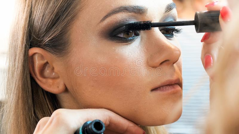 摆在年轻白肤金发的妇女特写镜头画象,当绘她的与染睫毛油时的化妆师眼睛 免版税库存照片