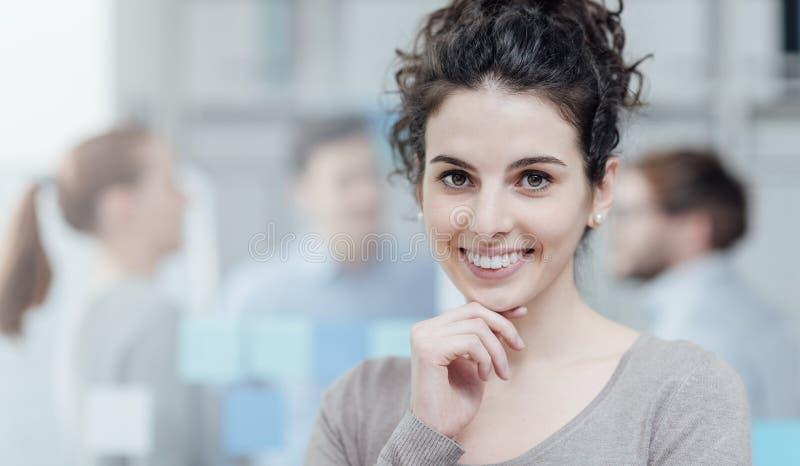 摆在年轻的办公室工作者微笑和 免版税库存照片
