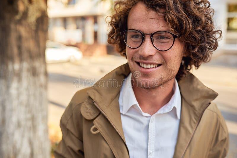 摆在年轻的商人特写镜头画象戴眼镜的微笑和户外 秋天街道的学院男生 聪明的人 免版税库存照片