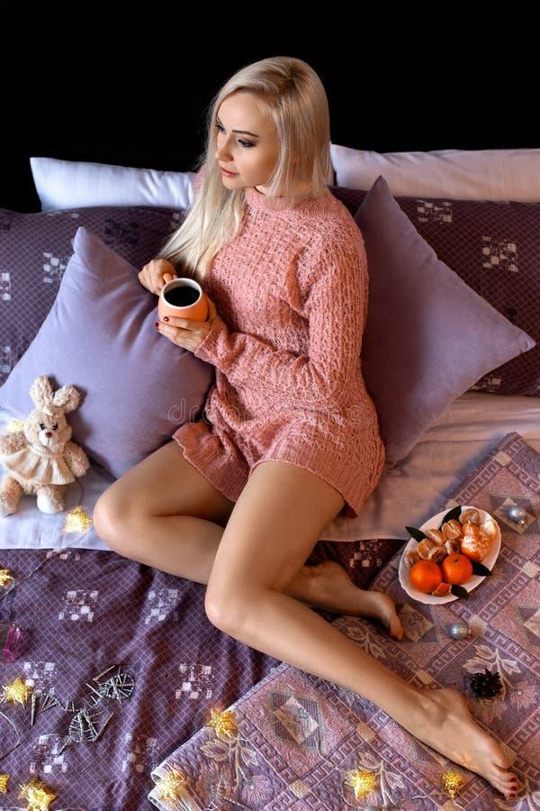 摆在床上的女孩用咖啡 库存照片