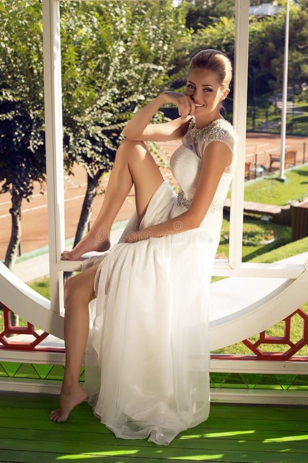 摆在庭院里的典雅的婚礼礼服的美丽的微笑的新娘 库存图片