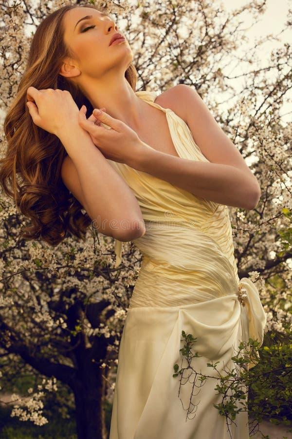 摆在开花公园的美丽的女孩 免版税库存照片